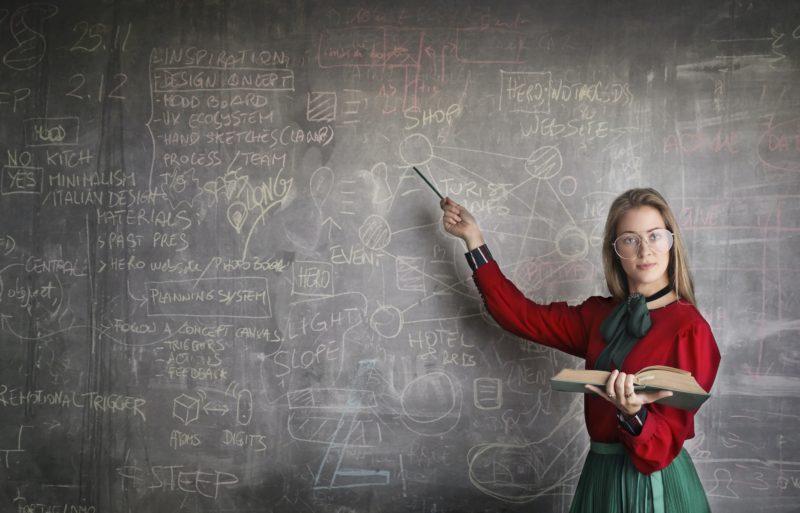 女性教師が黒板を指さす写真