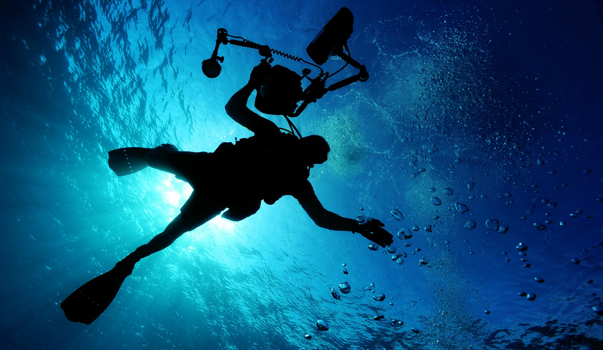 光差し込む水中でカメラマンダイバーがポーズする写真